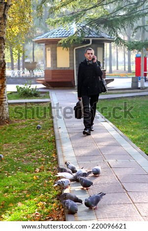 Young Man with Mobile Phone Walking in the Autumn Park - stock photo