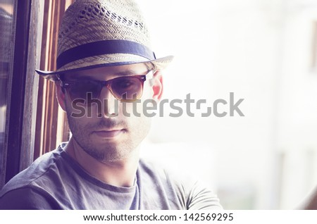 Young man with moder hat and sunglasses - stock photo