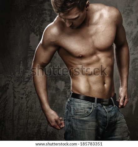 Young man with muscular  body in blue jeans - stock photo