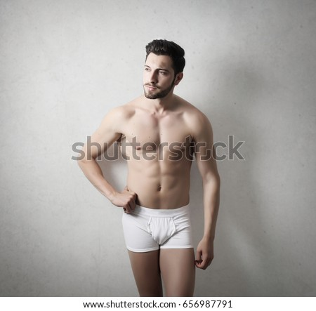 Young man with muscular body standing in his pants