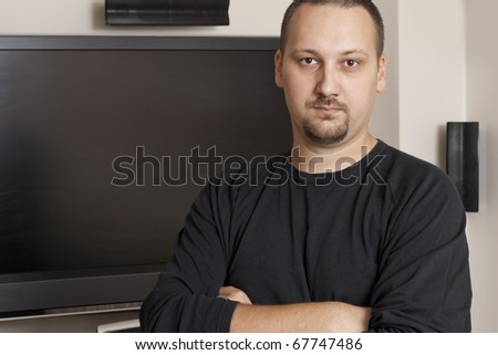 young man with mustache and beard standing in front of TV - stock photo