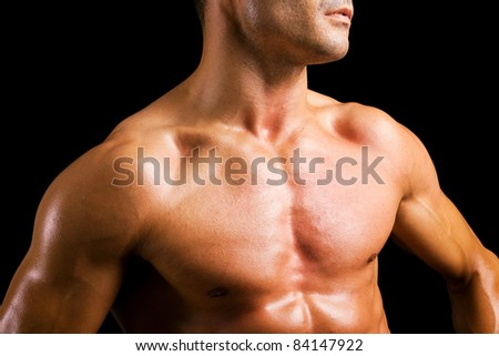 Young man with naked muscled torso against black background