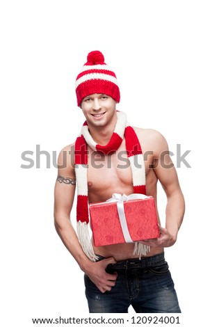 young man with naked torso holding red gift and sexy looking at camera isolated on white