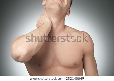 Young man with neck pain, isolated on white - stock photo