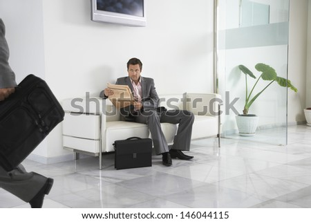 Young man with newspaper looking at cropped person in the office hallway - stock photo