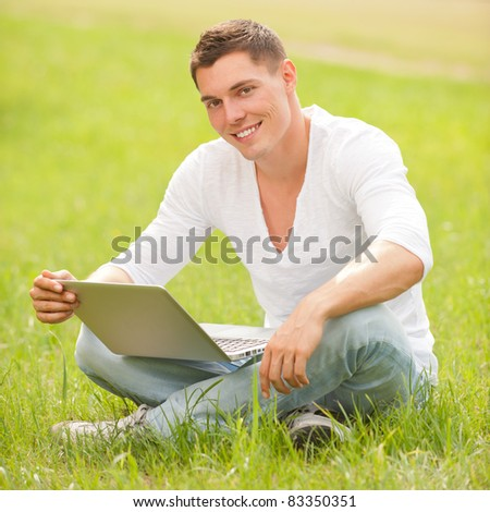 Young man with notebook in the park