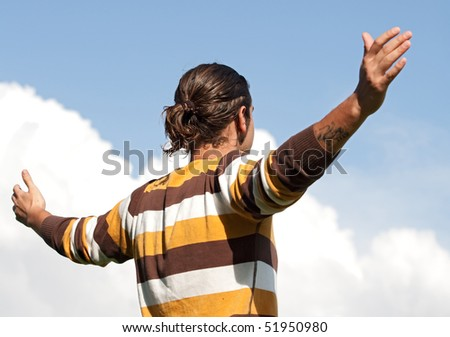 Young man with open arms on a blue sky with clouds