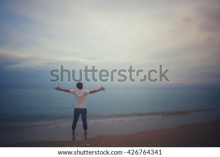 Young man with outstretched arms on sky background .filter color effect, copy space,selective focus.