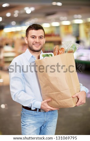 Young man with package of products in store - stock photo
