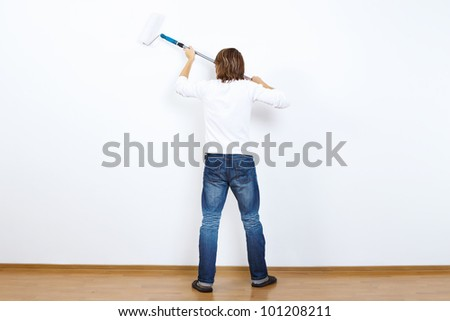 Young man with paint brush and blank white wall