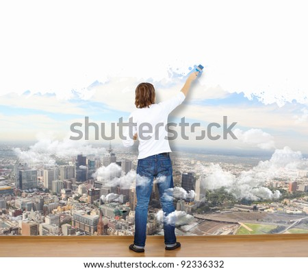 Young man with paint brush and wall with natural landscape - stock photo