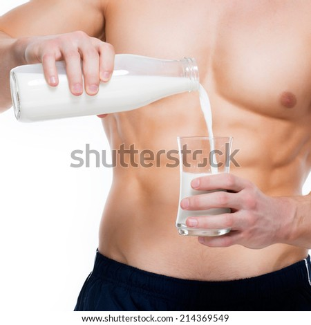 Young man with perfect body pouring milk into a glass - isolated on white background. - stock photo