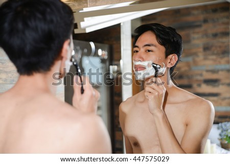 Young man with perfume looking to mirror at bathroom - stock photo