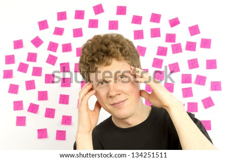 Young man with pink sticky notes and question mark thinking about decision making - stock photo