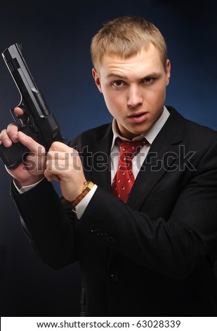 Young man with pistol over dark background - stock photo