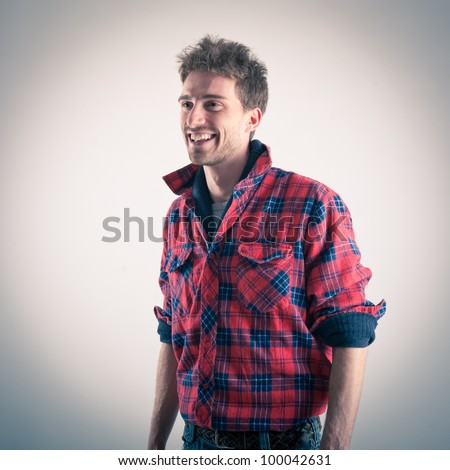 Young man with plaid shirt laughing. Studio shot. - stock photo