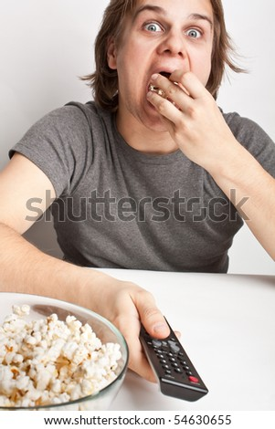 young man with popcorn and a remote control - stock photo