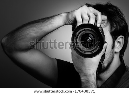 Young man with professional camera. Monochrome portrait