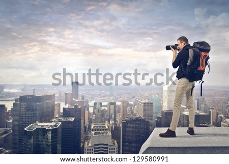 young man with professional camera photographing the city from the top - stock photo