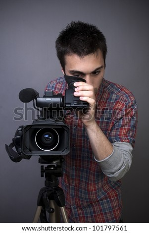 Young man with professional video camcorder on gray background - stock photo