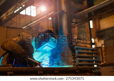 Young man with protective mask welding in a factory - stock photo