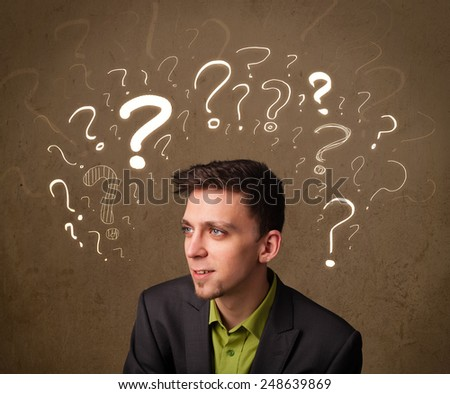 Young man with question mark symbols around his head - stock photo
