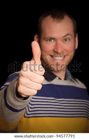 young man with raised eyebrow showing thumbs up. black background. focus on hand - stock photo