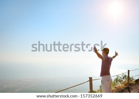 young man with raised hands on top of Vesuvius mountain looking for the horizon - stock photo