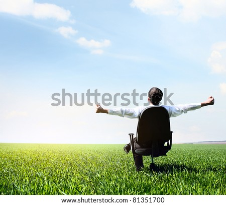 Young man with raised hands sitting in char on green meadow and looking to a sky with clouds - stock photo
