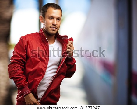 young man with red jacket against a city street background - stock photo