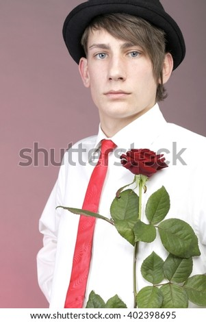 Young man with red rose flower. Love and reflection. - stock photo