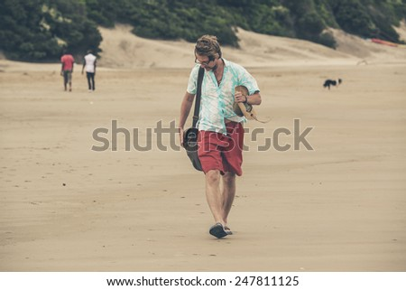 Young man with red shorts and blue shirt walking over beach.