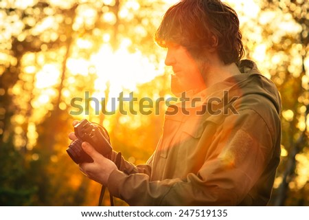 Young Man with retro photo camera outdoor hipster Lifestyle sunset forest nature on background - stock photo