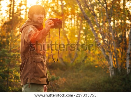Young Man with retro photo camera outdoor Lifestyle sunlight forest nature on background - stock photo