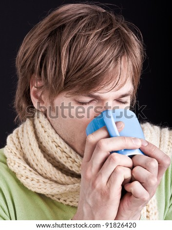 young man with scarf and hot drink