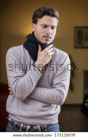 Young man with scarf, holding his neck because of throat ache, at home in his living room - stock photo