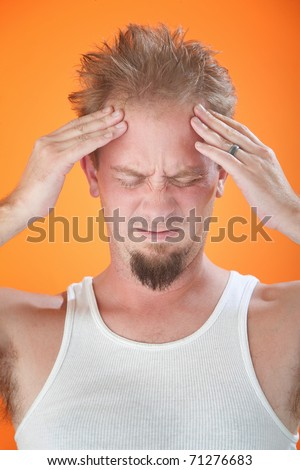 Young man with severe headache holds forehead - stock photo