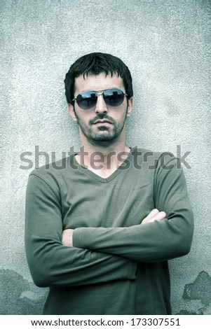 Young man with shades posing on white wall - stock photo