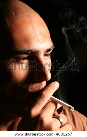 young man with shaved head smoking cigarette - stock photo