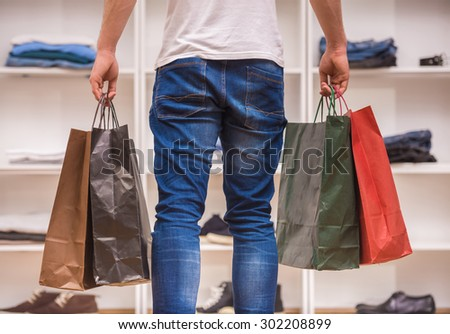 Young man with shopping bags in dressing room. Close-up. Back view. - stock photo