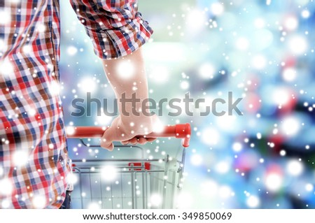 Young man with shopping cart in store over snow effect - stock photo