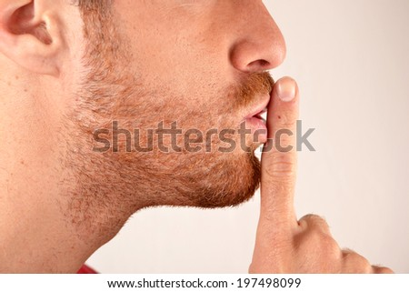 Young man with silence gesture - stock photo