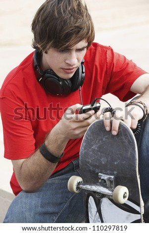 Young man with skateboard with cell phone