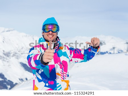 Young man with skis and a ski outfit in the Zillertal Arena, Austria. Focus on the finger - stock photo