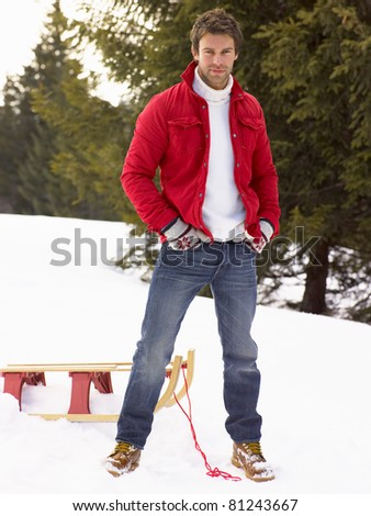 Young Man With Sled In Alpine Snow Scene - stock photo