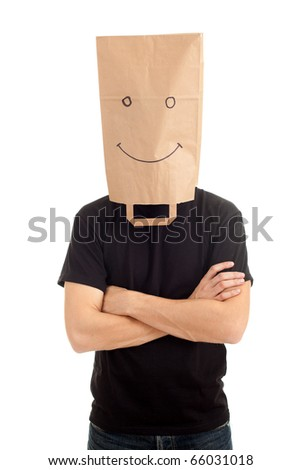 young man with smiling ecological paper bag on head and crossed arms - stock photo