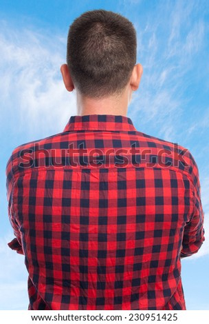 Young man with squares shirt over clouds background. He is giving his back - stock photo