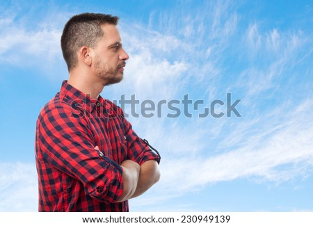 Young man with squares shirt over clouds background. He is showing his profile - stock photo