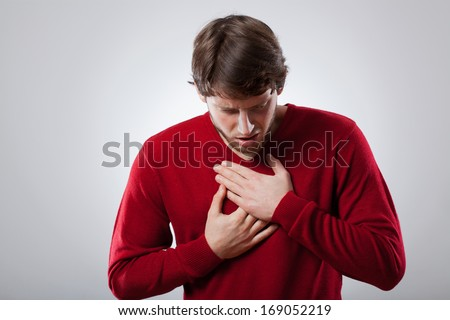 Young man with strong lungs ache holding his chest - stock photo