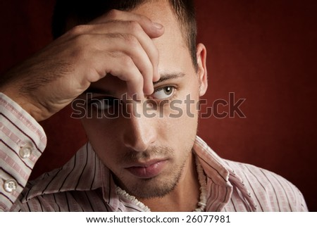 Young man with stubble in serious thought - stock photo